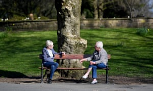 Two people sit apart on a park bench in  Ashton-Under-Lyne