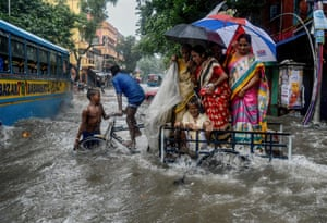 Kolkata, India A family tries to cross a flooded road amidst gushing water on Amherst street
