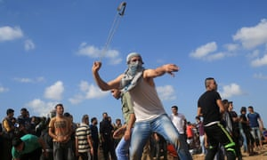 A protester uses a slingshot to throw stones