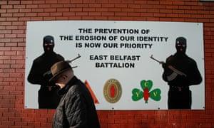 A man walks past a Ulster Volunteer Force mural on Belvoir Street