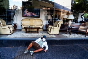 A homeless man sits in front of an interior design business in Buenos Aires, Argentina, 7 April.
