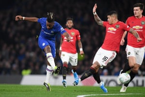 Michy Batshuayi of Chelsea scores his team's first goal as Marcos Rojo of Manchester United attempts to block.