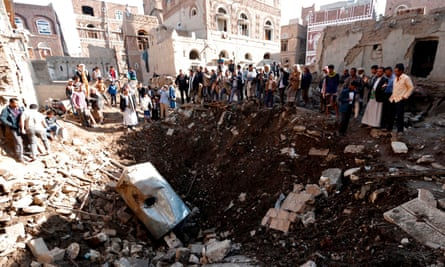 People look at the damage in the aftermath of an air strike in the Yemeni capital of Sanaa on 11 November.