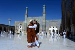 Men hug after praying at the Jami mosque