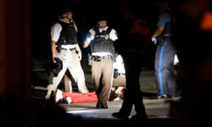 A black man lies badly wounded with blood on his shirt