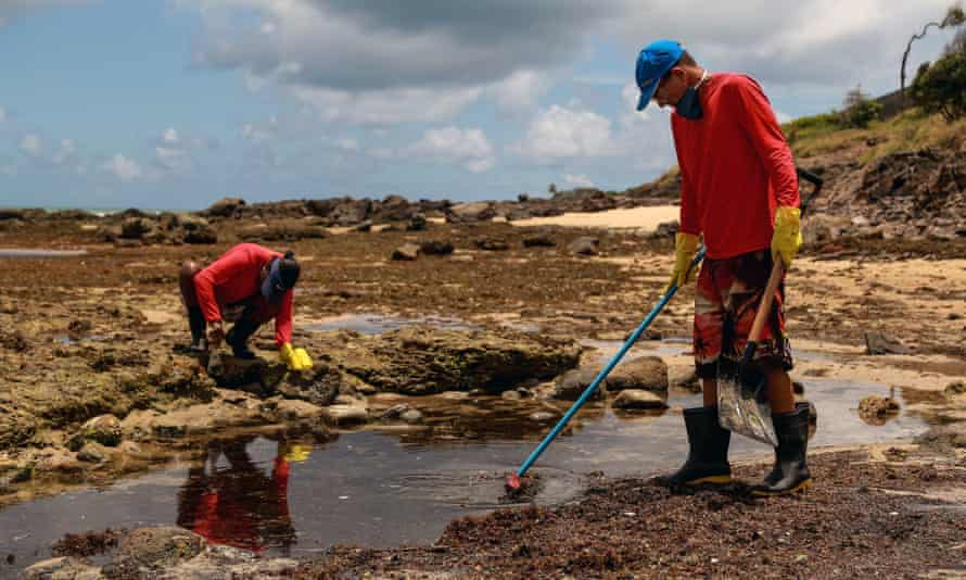 Volunteers help in the work to recover oil at the Itapuama beach, in Cabo de San Agostinho, Brazil, on Tuesday.