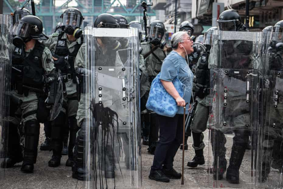 A woman shouts at police officers as they advance towards protesters in Hong Kong in July 2019.