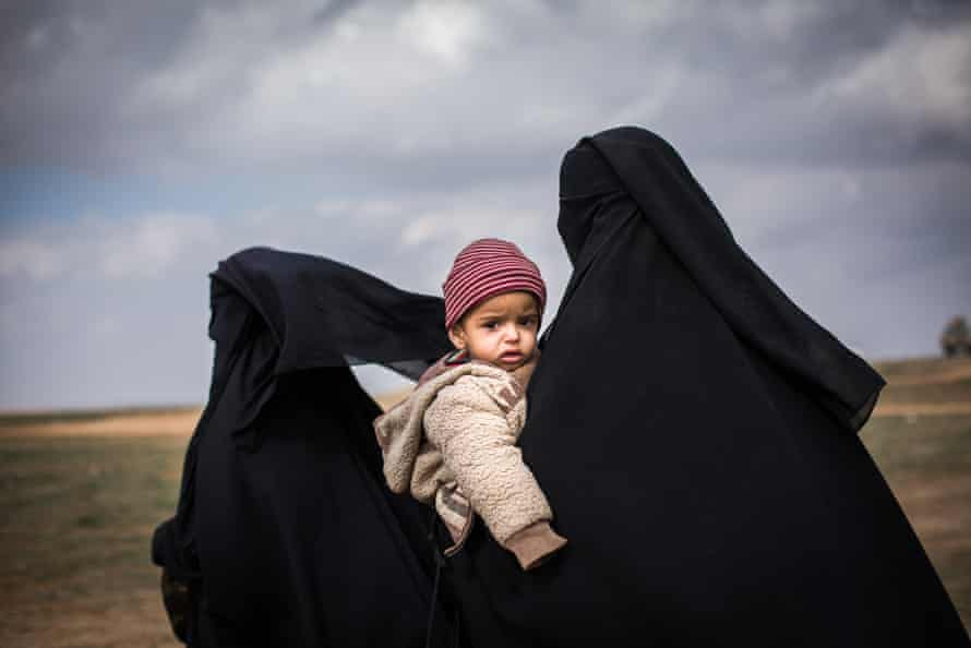 A woman clutching her young child is seen at a civilian screening point for ISIS families fleeing heavy fighting in the city of Baghuz, on 9 February 2019