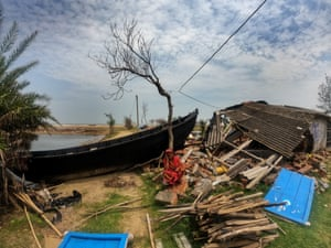 Kolkata, India: A woman sits on the remains of her house, which was destroyed by Cyclone Yaas.