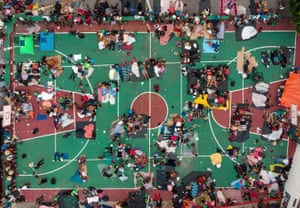 Aerial view of Honduran migrants heading in a caravan to the US, resting in a basketball pitch in San Pedro Tapanatepec, Oaxaca state, southern Mexico