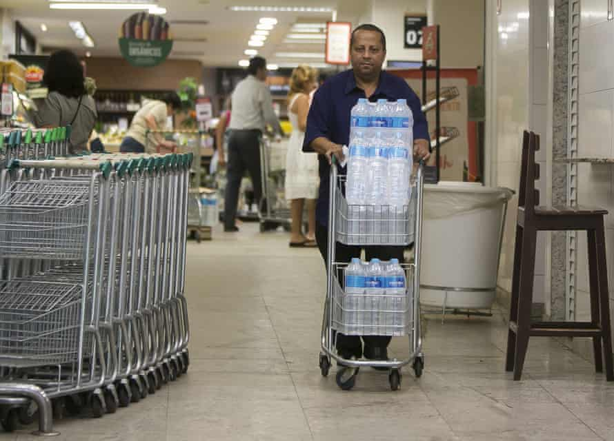 Almir Vicente pushes a cart filled with water. Residents in Rio de Janeiro are alarmed by murky, smelly water coming from their taps.