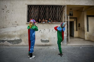 Palestinian youths dressed as clowns stage a street performance to entertain children trapped at home due to the coronavirus outbreak in Khan Yunis.
