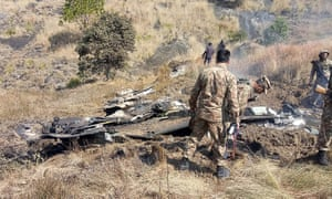 Pakistani soldiers stand next to the wreckage of an Indian fighter in Pakistan-controlled Kashmir.