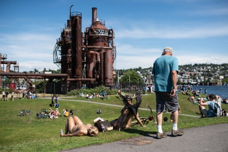 A spectator passes nude cyclists at Gas Works park.