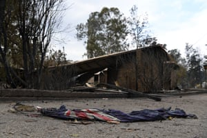 A charred australian flag lies in front of a burnt-out residence in Sarsfield, East Gippsland, Victoria.