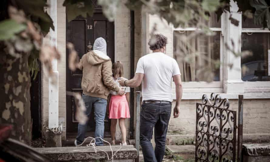 Man and woman lead a child into a house