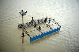Children of local boatmen play on top of a submerged restroom at Daraganj Ghat on the flooded banks of the Ganges river.