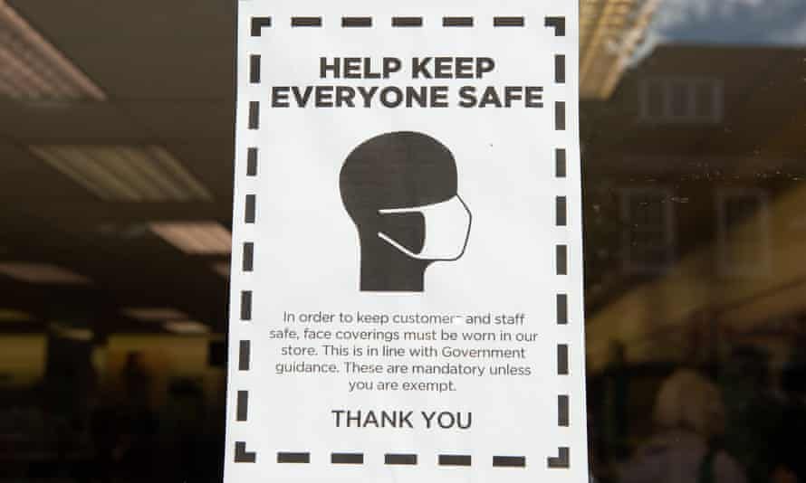 A sign in a shop window reading 'Help keep everyone safe', asking customers to wear a mask