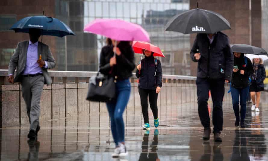 Commuters cross London Bridge in central London as weather warnings.