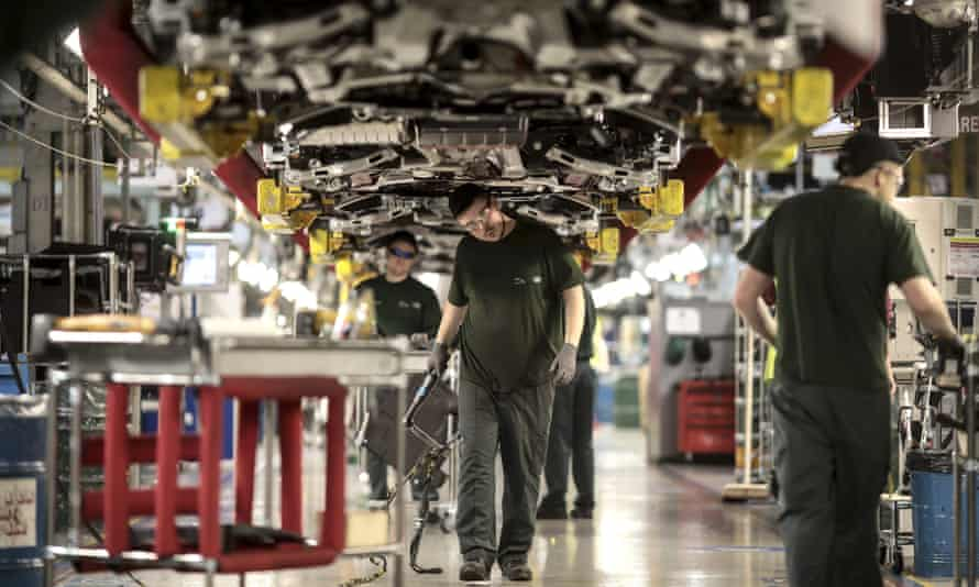 Employees work underneath Jaguar automobiles on the final assembly line at Tata Motors Ltd.'s Jaguar assembly plant in Castle Bromwich