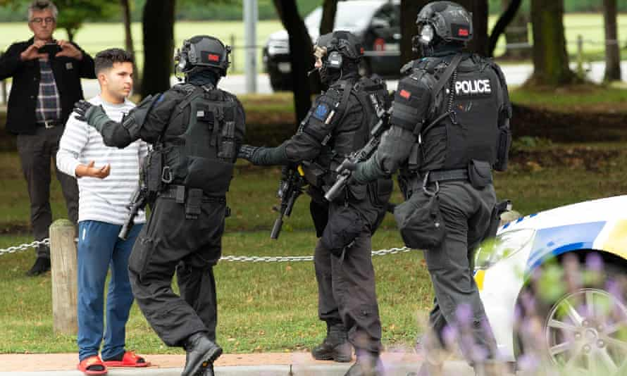 Members of the armed offenders squad push back members of the public from the scene of one of the attacks in Christchurch.