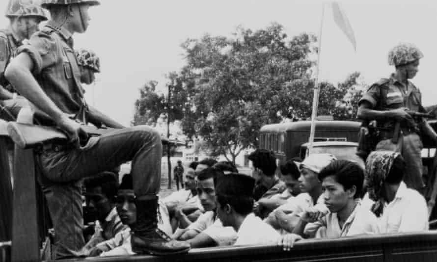 Members of the youth wing of the Indonesian Communist party are watched by soldiers as they are taken to prison in Jakarta on 30 October 1965.