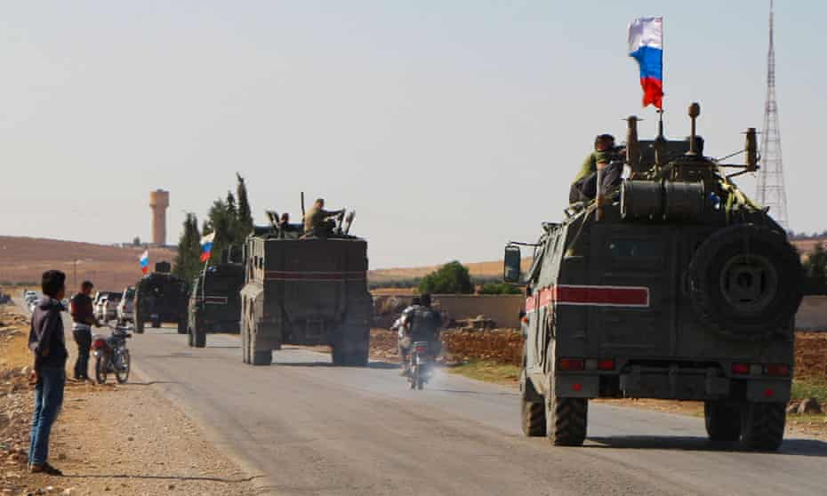 A convoy of Russian military vehicles drives towards the Syrian town of Kobane