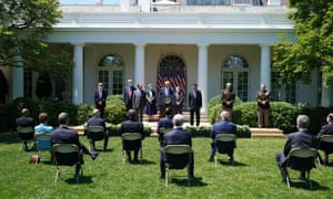 Press and observers watch the president's remarks from spread out seats in the Rose Garden of the White House