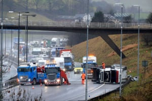 Recovery workers prepare to right an overturned lorry at the scene of an accident on the eastbound track of the M62 motorway between junctions Milnrow and Ripponden