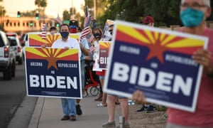 """Members of the group """"Arizona Republicans Who Believe In Treating Others With Respect"""" wave flags and hold signs in support of Democratic presidential candidate Joe Biden, during evening rush hour in Phoenix"""