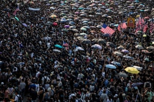 Tens of thousands of protesters walk through central district during a march to petition the US consulate.