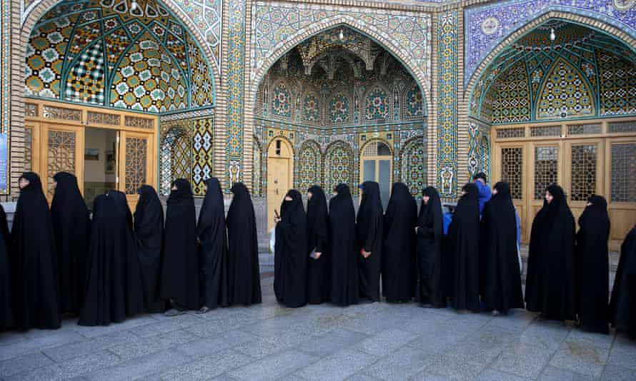Iranian women stand in line at a polling station