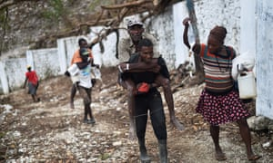 A man with cholera symptoms is carried to a small clinic in Randelle, Haiti, on 19 October 2016