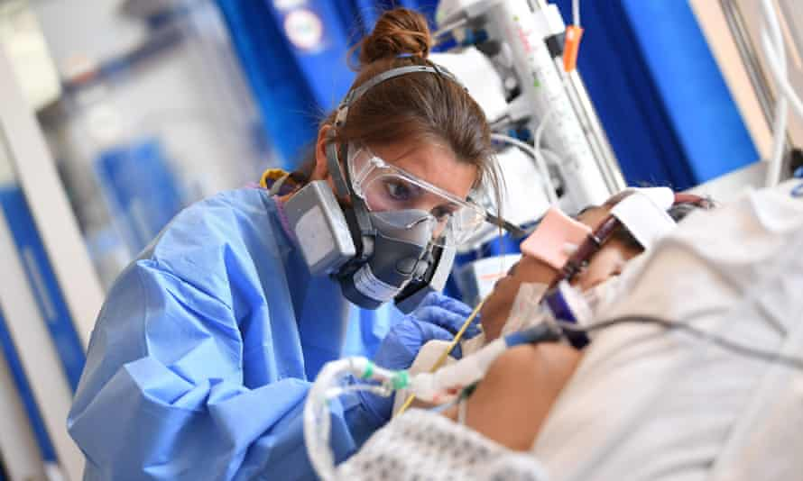 A health worker wears PPE as she cares for a patient in the intensive care unit at Royal Papworth hospital in Cambridge.