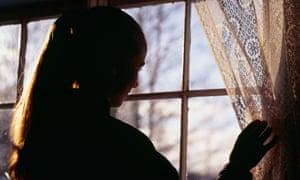 Silhouette of a young woman looking through window