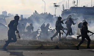 Members of the Bolivarian National Guard loyal to Venezuelan President Nicolas Maduro run under a cloud of tear gas after being repelled with rifle fire by guards supporting Venezuelan opposition leader