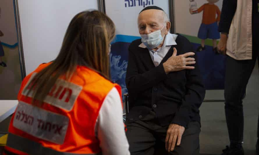 A 92-year-old man prepares to be vaccinated at a sports arena in Jerusalem on 21 January.