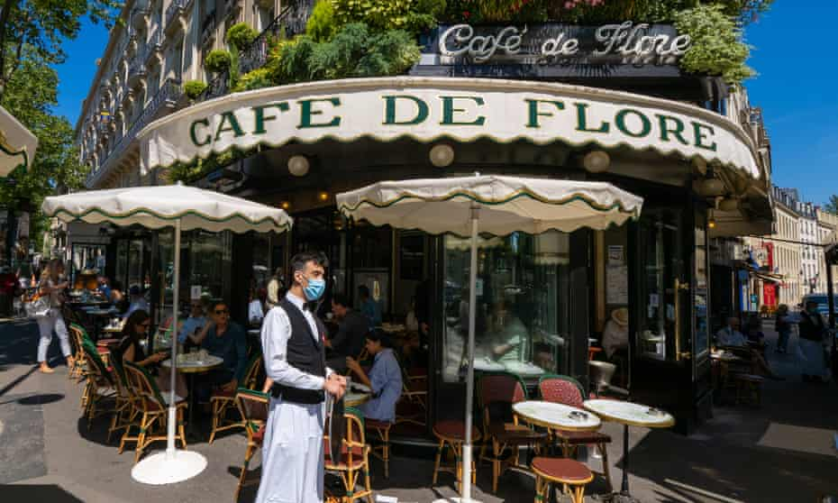 A waiter at the newly reopened Café de Flore in Paris wears a mask as he serves customers seated outside.