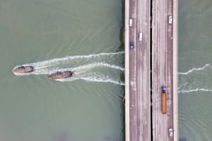 Fishing boats travel under a bridge near Tianjin