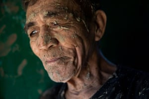 A man takes a break from cleaning mud from his house after flooding caused by Typhoon Vamco.