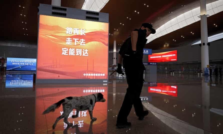 A policeman and his dog patrol at the immigration building for the China-Zhuhai-Macau-Hong Kong Bridge ahead of the opening ceremony in Zhuhai