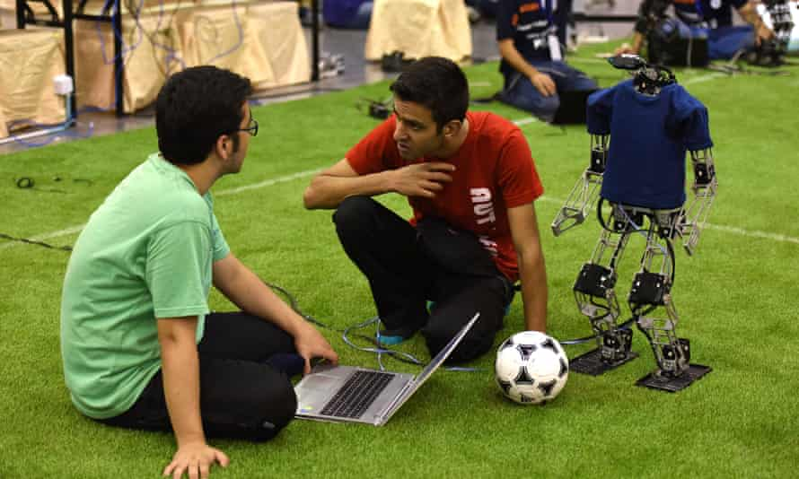 Robot programmers confer at Robocup 2015, in China.