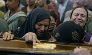 Relatives react during the funeral of one of the people killed after a bus carrying Coptic Christians was attacked in Egypt's southern Minya province.