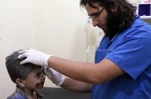 A wounded boy receives medical treatment at a field hospital
