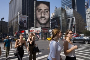 People walk past an advertisement featuring Colin Kaepernick in New York.