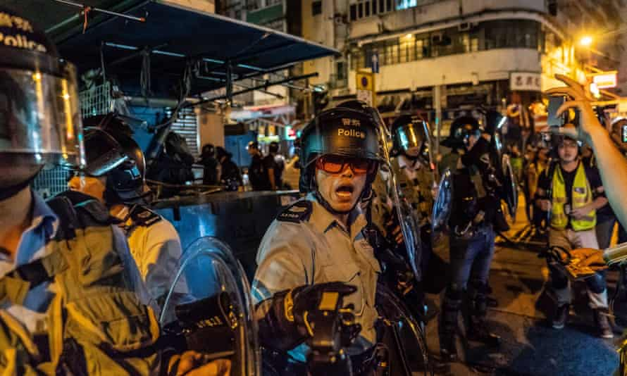Riot police point pepper spray in the direction of protesters during clashes in Sham Shui Po