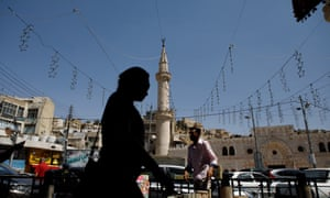 A woman passes a street vendor and a minaret in Amman, Jordan