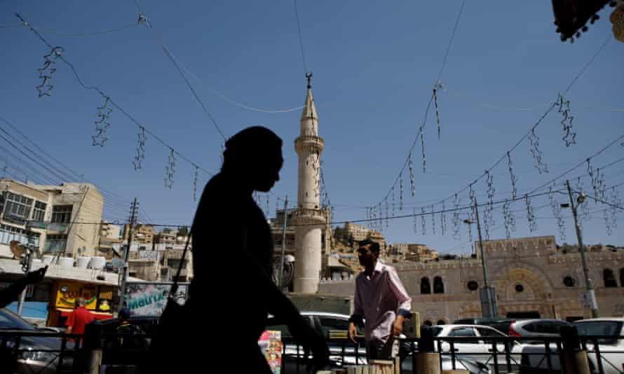 A woman passes a street vendor and a minaret in Amman, Jordan