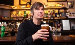 Ian Rankin holding a pint sitting at a bar
