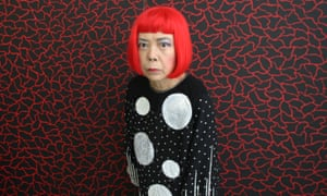 Yayoi Kusama stands in front of one of her paintings in her studio.